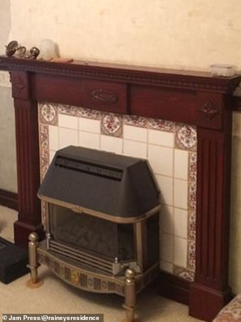 The living room fireplace pictured before it was ripped out and replaced with a more stylish black fireplace inside a cream mantel