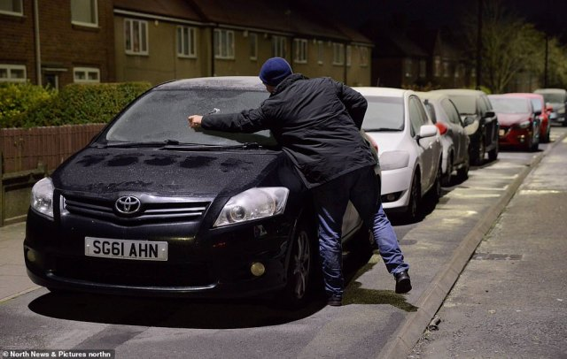 A man scrapes the ice from the windscreen of a car in Newcastle-upon-Tyne this morning after a frosty night