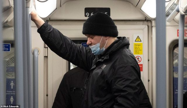 A man travels on the London Underground's Jubilee line this morning while wearing a face mask pulled below his nose