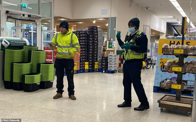 Security checking people are wearing masks at a supermarket in Peckham, South East London this morning