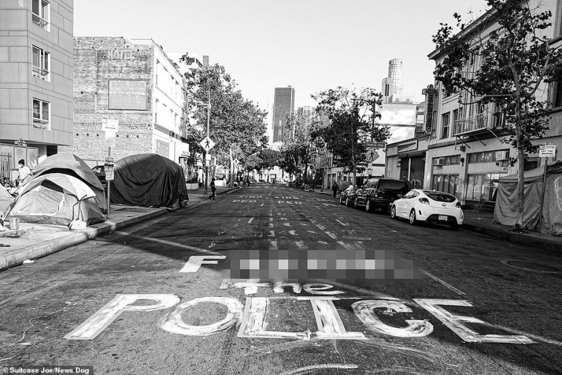 Graffiti on the road says 'F*** the Police', making it clear the neighbourhood's attitude towards authority
