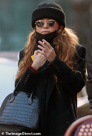 Mary-Kate Olsen was spotted out with friends in New York City in the fall wearing a black beanie, matching trench coat, and boots