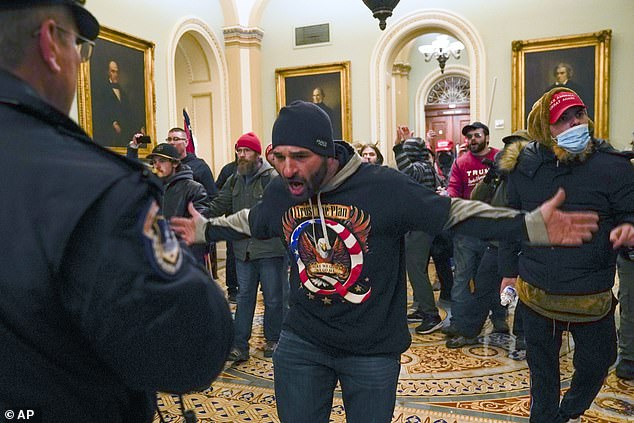 As Jensen chases Goodman, he and the mob are met by a group of police in a back corridor outside the Senate. Jensen was later arrested and faces federal charges. Pictured: Trump protesters gesture to police outside the hallway