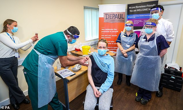 Kelly Heney pictured with NHS staff giving her an injection of the Covid-19 vaccine at the Depaul UK homeless shelter in Oldham, Greater Manchester, as the council and GPs launch an effort to vaccinate homeless people in the town to protect them from the virus