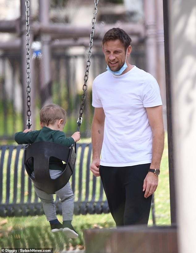 Cute: Jenson adored Hendrix as he pushed him into a pram before heading to a swing with the toddler