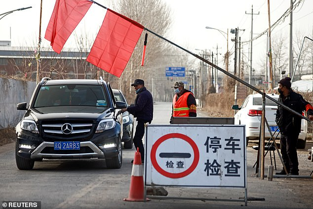 Volunteers stop a car at a checkpoint on a road leading into their village, following the coronavirus outbreak, on the outskirts of Beijing