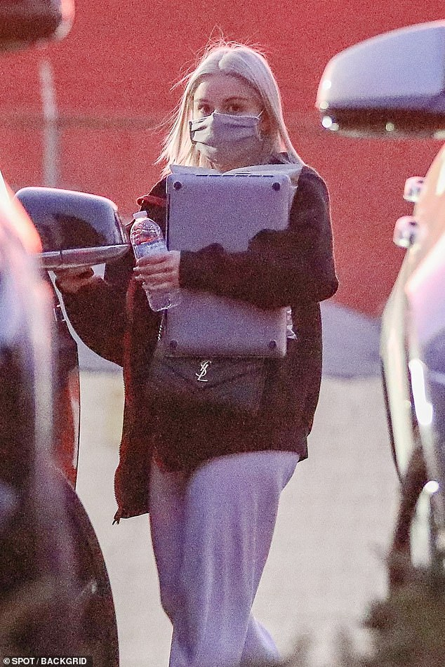 Outside: Ariel Winter was spotted carrying a laptop while shopping in Los Angeles on Wednesday with stylish dyed blonde hair and a face mask.