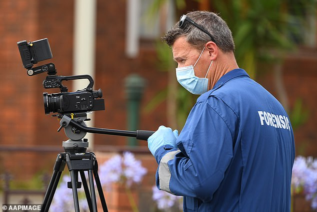 Forensic officers are seen at work at a crime scene in Tullamarine
