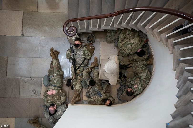 The troops cradled their weapons and huddled together as they slept inside the Capitol on Wednesday