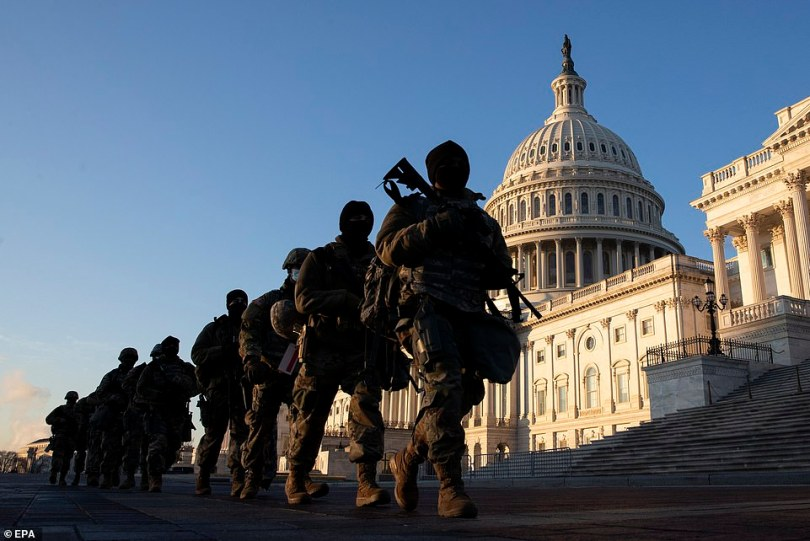 Armed National Guard troops are seen outside the U.S. Capitol Building as members inside debate impeaching President Donald Trump for a second time in 13 months