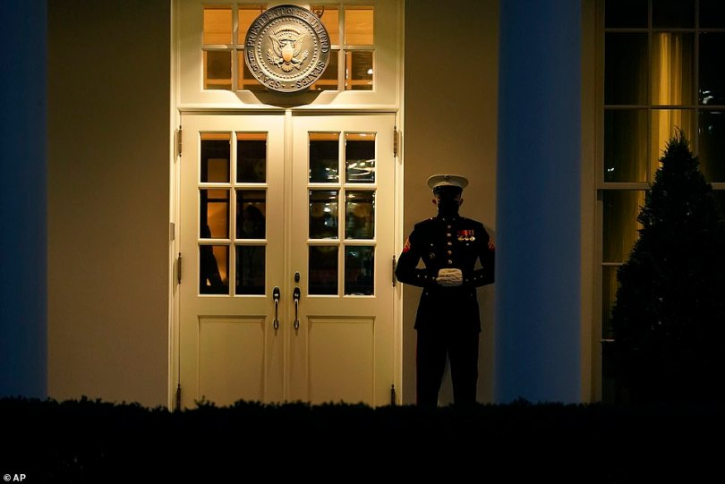 A Marine guard stands at the entrance to the West Wing of the White House on Wednesday night. The guard's presence signifies the president is likely in the Oval Office