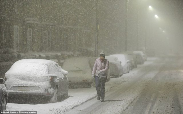 A woman braves the blizzard conditions in Consett, County Durham, this morning  as the snow continues to fall
