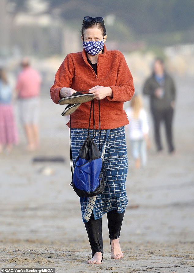 Outdoors: The Aliens actress donned an orange fleece comforter over her wetsuit and donned a blue mask as she walked the beach after a swim in the ocean.