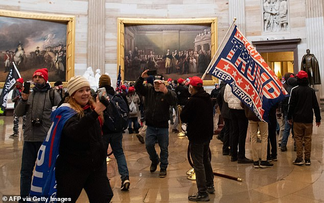 Jenny Cudd, on the left of the picture wearing a Trump flag, was among the mob who invaded the Capitol on Wednesday - and boasted that she was 'proud' to have taken part in the intrusion egged on by the president