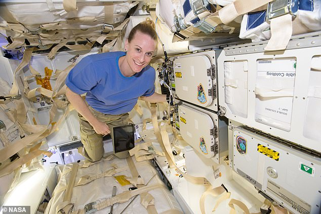 NASA astronaut Kate Rubins poses next to storage in the SpaceX CRS-9 cargo Dragon spacecraft in 2016. The new cargo spacecraft has more powered locker space, enabling additional cold stowage space
