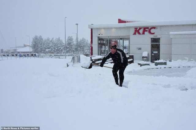 KFC workers struggle to clear snow to enable customers to access their drive-thru today in Consett, County Durham
