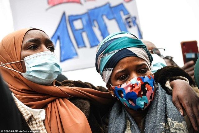 Ibrahima B's mother (R) takes part in a demonstration on January 13, 2021 outside the police station in Brussels where her son was being held when he collapsed