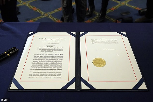 The article of impeachment against President Donald Trump sits on a table before House Speaker Nancy Pelosi at an engrossment ceremony after Wednesday's vote