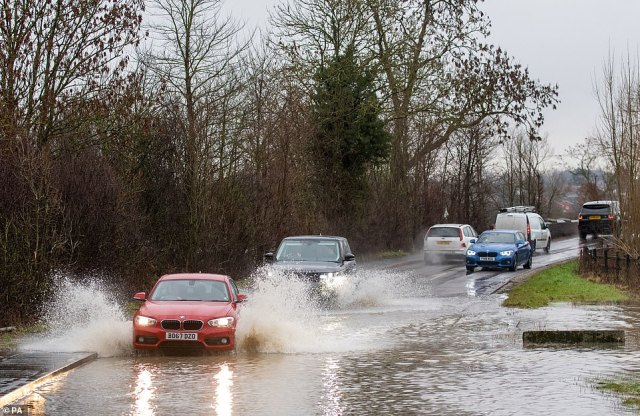 Cars pass through a flooded road in Loughborough this afternoon, as heavy rain falls in much of England today