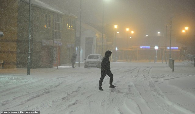 A pedestrian walks across a road during blizzard conditions in Consett, County Durham, this morning