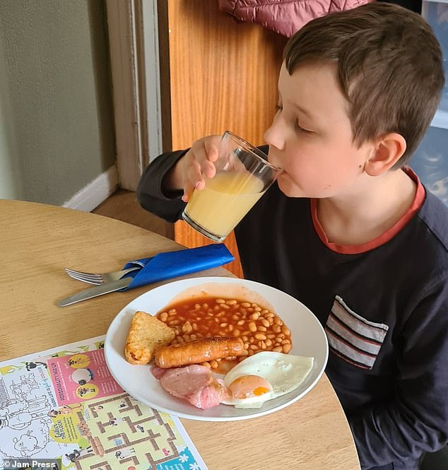Stacey Brooks' son Josh, nine, is pictured enjoying the cooked breakfast of beans, bacon and egg