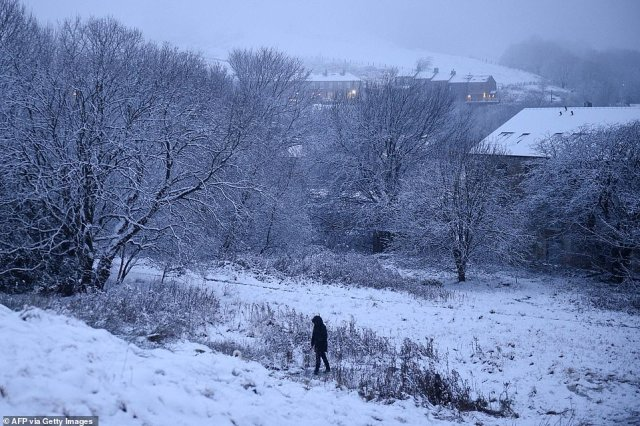 A walker makes their way up a snow covered hill in Marsden, northern England