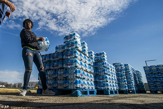 Flint's troubles began in 2014 after the predominantly African-American city switched its water supply to the Flint River from Lake Huron to cut costs (Pictured: volunteers load cases of water into vehicles in Flint)