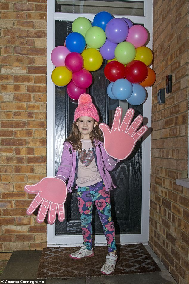 Dorrie Cunningham, aged eight, claps with giant hands in Bookham, Surrey