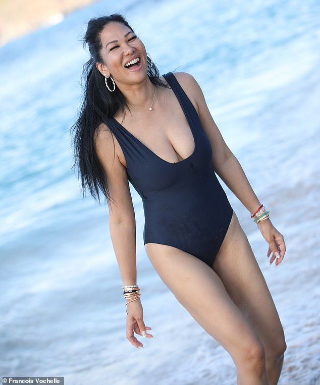 Ooh la la:The Baby Phat visionary was happy to show off her toned figure in the simple suit, which dipped low to offer a generous amount of cleavage