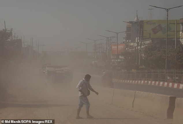 A Bangladeshi refugee with asthma has avoided deportation from France after a court ruled that pollution in his native country would aggravate his condition and potentially kill him. Pictured, a man crossing a dusty road in Dhaka, Bangladesh
