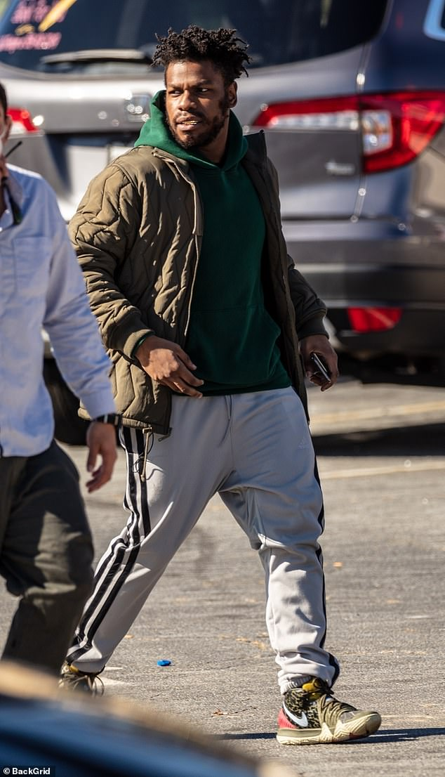 Casual: Boyega wore an olive green bomber jacket, white joggers and multi-colored Nike sneakers and appeared to be driving Parris in one scene