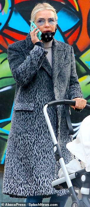 Fierce look: She also sported a chic look in a knee-length grey cheetah-print overcoat