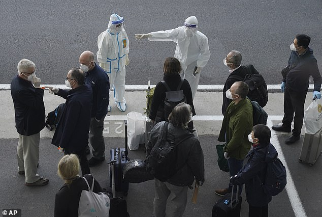 A Chinese official wearing a hazmat suit and goggles directs members of the WHO expert panel of investigators on their arrival at Wuhan airport on Thursday