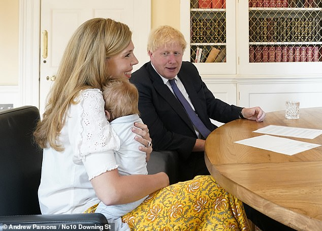 A television company is planning to feature Boris Johnson's love child in an upcoming documentary about his first year in office. Pictured: The Prime Minister and his fiancée Carrie Symonds speak to the midwifes that helped deliver their son Wilfred at University College Hospital in London in July last year