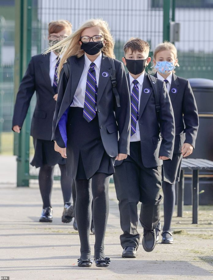 Despite the UK recording another drop in Covid cases, school bosses believe millions of pupils face being home schooled until the start of April. Pictured: Pupils wear protective face masks