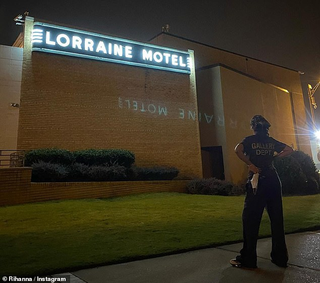Looking up:The Work singer in another photo stood on a sidewalk with her hands on her hips and her back to the camera while looking up at a museum building with a neon white Lorraine Motel sign on top