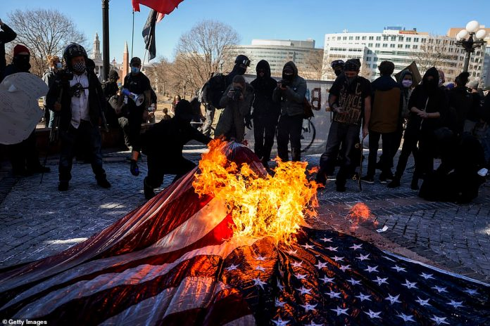 COLORADO: Members of the Communist Party USA and other anti-fascist groups burn an American flag on the steps of the Colorado State Capitol in Denver on Wednesday