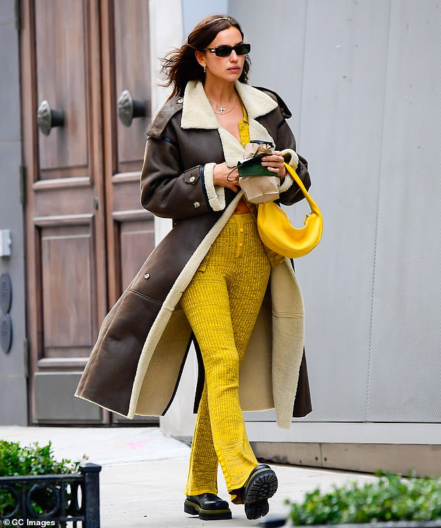 Excellent contrast: Shayk paired a yellow-dominant outfit with a large brown overcoat to stay comfortable while she was spending time outside