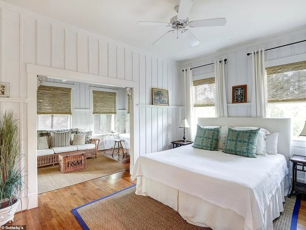 The master bedroom has a seating room and feels an old plantation style with antique accents and dark wood furnishings