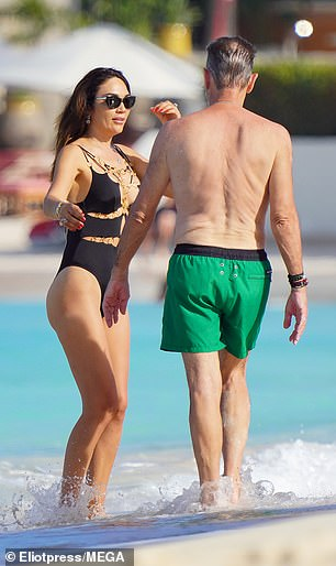 Chatty: The happy couple were seen talking on the beach before taking a photo together