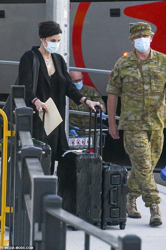 Mandatory: Flanked by a guard, she was taken and embarked on transport to her mandatory 14-day hotel quarantine