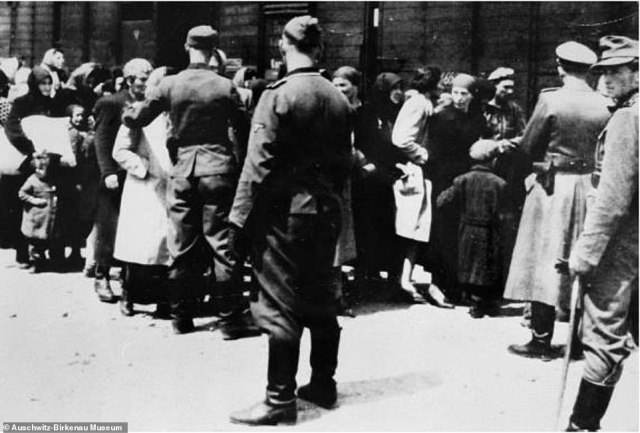 SS guards are seen supervising the arrival of a transport of Hungarian Jews shortly after their arrival at Auschwitz-Birkenau. Pictured far right is SS member Stefan Baretzki. He was conscripted into the SS and stationed at Auschwitz between 1942 and 1945. Author Mr Baxter said Baretzki 'participated in mass murder by making selections, and was unrestrained in his beating of prisoners'