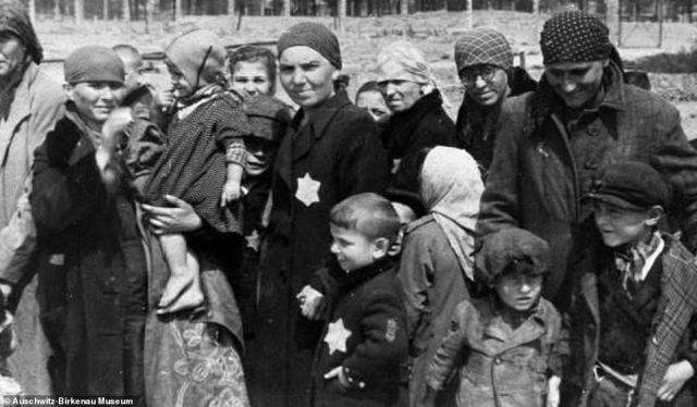 These Hungarian Jewish women and children are seen looking at the camera as their picture is taken. To the right, a mother can be seen smiling down at her children. In the centre of the image, a mother clutches her child's hand. These people had been selected for death, rather than work, after arriving at Auschwitz-Birkenau