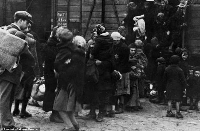 Women and children are seen above jumping from the freight trains shortly after their arrival at Auschwitz. Among them is a boy seen holding a younger child in his arms. In the foreground, a young man wearing a hat looks at a woman who is also holding a child