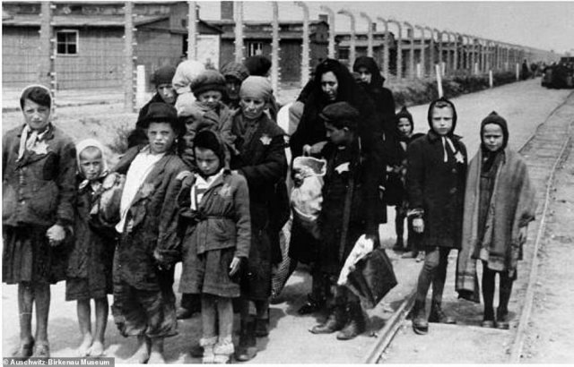 These women and children still wearing the clothes they arrived in are seen standing shortly after being selected for death at Auschwitz-Birkenau