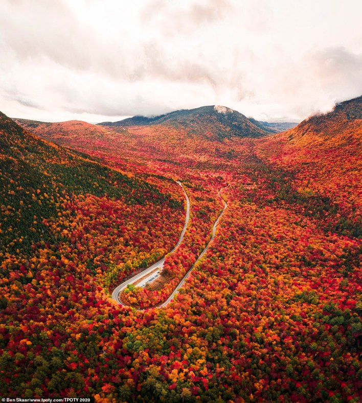 Hue goes there: This incredible shot of an autumnal New Hampshire was taken by the overall young photographer of the year 15-18, American Ben Skaar, who's 17. He said: 'I slept in my car for two nights to get this shot. I drove up to the White Mountains hoping to capture the vibrant autumn colors. I woke up at 4:30 that Sunday morning and, as the sun rose over the mountains, the colors seemed to be set ablaze'