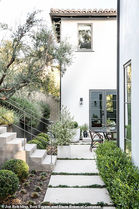 Chic exterior: A white plaster exterior features a red terra-cotta roof, surrounded by lush green landscaping and a cement pathway