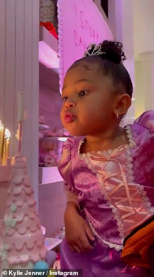 Make a wish: Kylie leaned in with Stormi to let her blow out the candles atop her extravagant castle cake