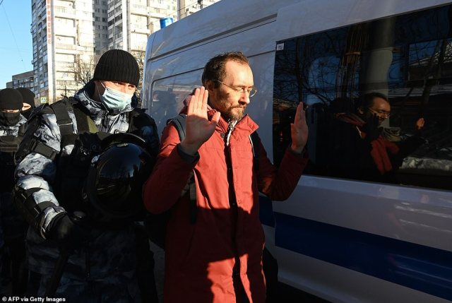 Riot police lead a Navalny supporter towards a waiting van this morning