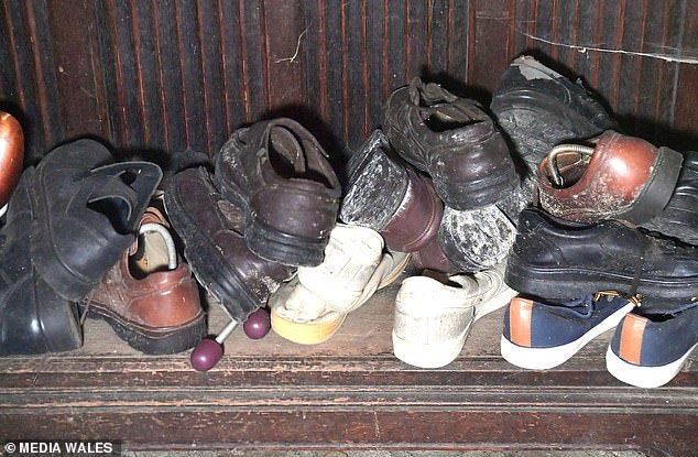 Each space is strewn with personal possessions and furniture from past decades, and this continues on the two upper floors where the bedrooms and bathroom are located. There are clothes still on hangers in the bedrooms, photo frames and shoes in the cupboard (pictured)